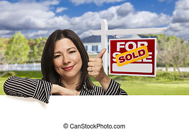 Hispanic Woman in Front of Sold For Sale Sign, House -...