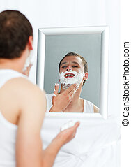 Man shaving in bathroom - Happy young man shaving in...