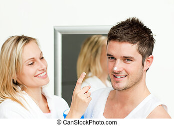 Happy man with cream in his nose with her girlfriend in...