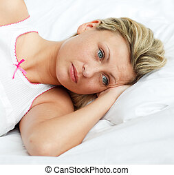 Portrait of upset woman lying in bed