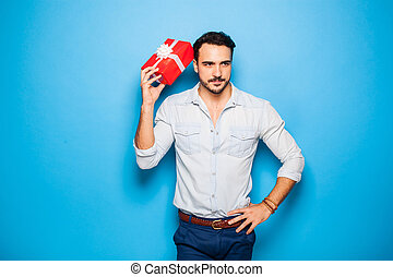 handsome adult man on blue background with christmas gift -...