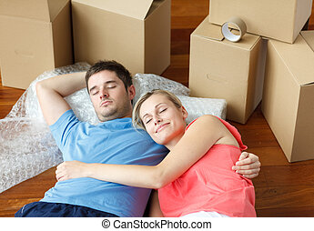 Happy couple sleeping on floor after moving house