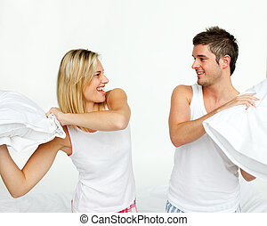 Young couple fighting with pillows in bed