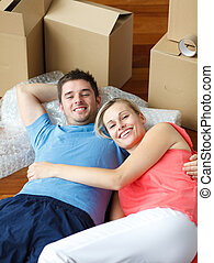 Happy couple lying on floor after moving house