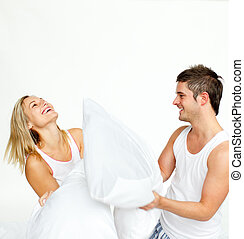Young couple having a pillow fight with copy-space - Young...