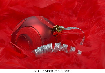 christmas ball over red feathers