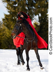 beautiful woman with red cloak with horse outdoor in winter