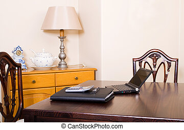 laptop in a living room - a laptop on a desk beside a...