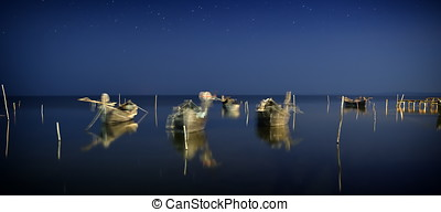 fishing boats on the lake by night - long exposure image