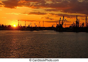 Bright Colorful Sunset at Cargo Sea Port with Black Cranes...