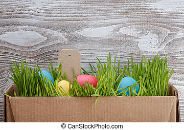 easter eggs in box with fresh grass over wood background,...