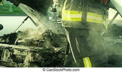 Firefighters tries to extinguish the fire on the parking...