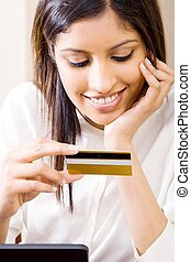 woman with bank card - a woman smiling down at her credit...
