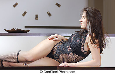 attractive woman laying down on a table in the kitchen