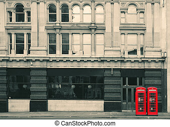 Red telephone booth in street with historical architecture...