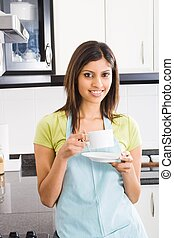 woman drinking coffee at home - an indian woman drinking...