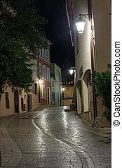 Narrow old street at night in Saint-Tropez, France.