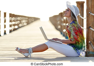young woman using laptop outdoor in summer - young smiling...