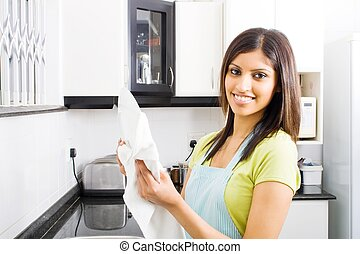 indian woman in kitchen - an indian woman in kitchen drying...