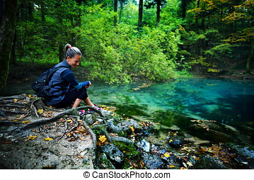 caucasian woman tourist relaxing by the river, in the...