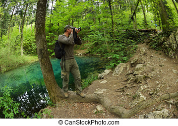 photographer visiting beautiful pond in the woods, Ociul...