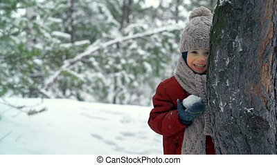 Amusing Game - Little boy playing snowballs with someone out...