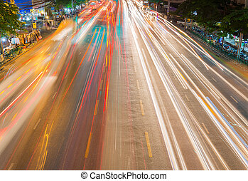 light streams from ongoing traffic in business district road