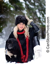 pretty woman with black dog outdoor in winter