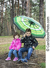 Spring in the woods on a stump sits a boy with a girl under an u