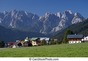 Beautiful sunny day in Alps with green meadows, village and...