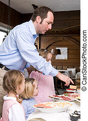 Breakfast in a small hotel - Father with daughters at...