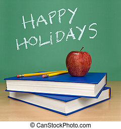 Happy holidays written on a chalkboard Books, pencils and an...