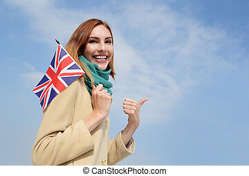 happy young travel woman holding British England flag with...