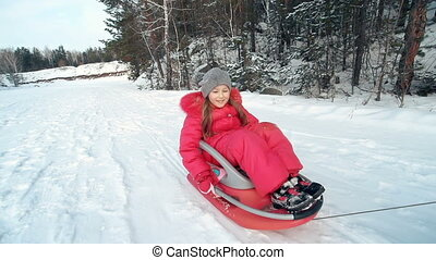 Weekend Outdoors - Little girl in toboggan pulled by cropped...