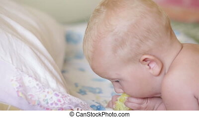 child eat corn lying on a bed - small blonde baby girl eat...