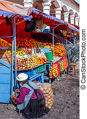 Market stall in Ecuador - Woman crouching in front of her...