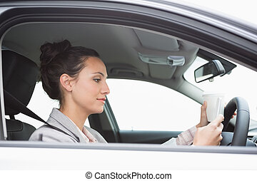 Young businesswoman having a coffee in her car