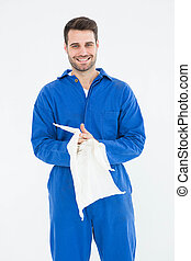 Male mechanic wiping hands with cloth - Portrait of smiling...