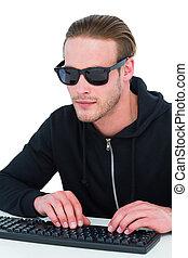 Unsmiling hacker typing on keyboard