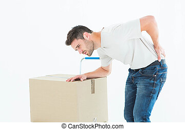 Delivery man with cardboard box suffering from backache -...