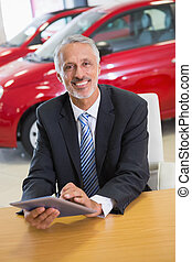 Smiling businessman using tablet at his desk at new car...