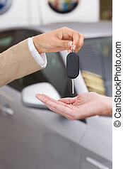 Businesswoman giving car key to happy customer at new car...