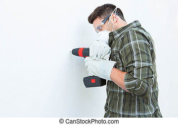 Carpenter using drill machine on white wall - Side view of...