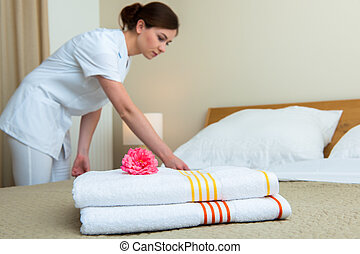 Maid making bed in hotel room - Hotel room service. Young...