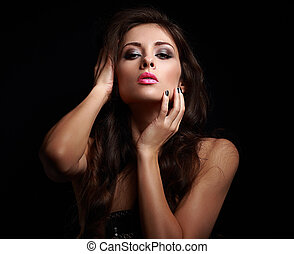 Hot sexy woman in dark touching her makeup face on black