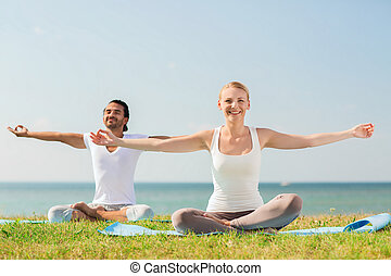 smiling couple making yoga exercises outdoors - fitness,...