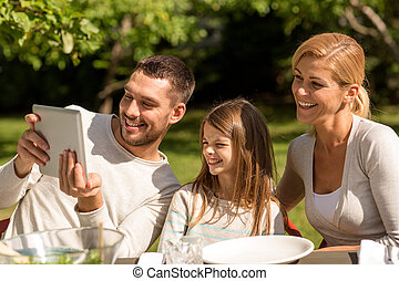 happy family with tablet pc outdoors - family, happiness,...