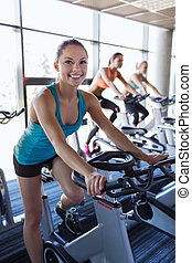group of women riding on exercise bike in gym - sport,...
