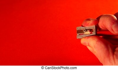 Pencil sharpener and a red pencil on a red background