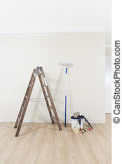 Repaint wall - Painting supplies with ladder against a wall...